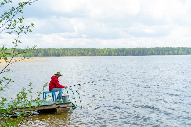 川のほとりに釣り竿をかぶった帽子をかぶった漁師が座っている。