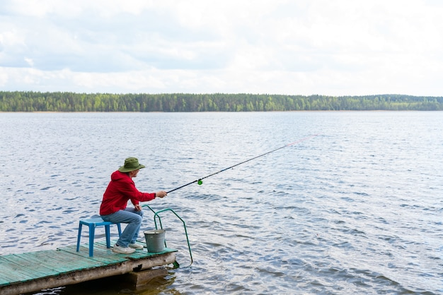 Рыбак в шляпе с удочкой сидит на берегу реки.