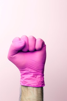 医療用手袋の拳。明るい背景の上のピンクの医療用手袋の医師の手。