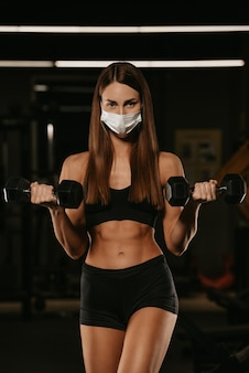 코로나바이러스의 확산을 피하기 위해 안면 마스크를 쓴 건강한 여성이 아령으로 이두박근을 하고 있습니다. 수술용 마스크를 쓴 스포티한 소녀가 체육관에서 팔 운동을 하는 동안 포즈를 취하고 있습니다.