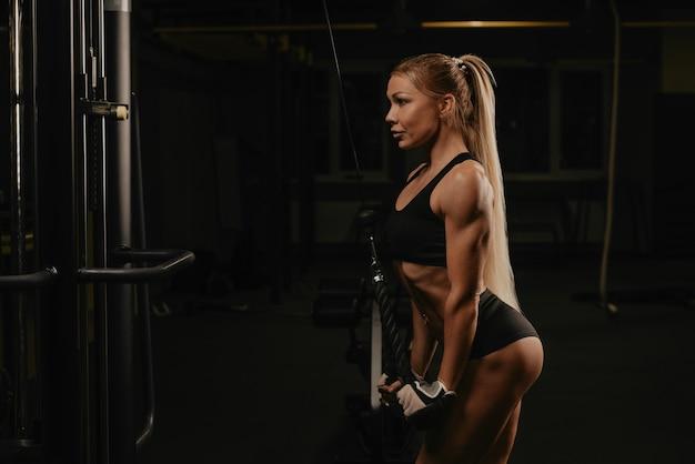 Спортивная женщина с длинными светлыми волосами делает отжимание на трицепсной скакалке в тренажерном зале. девушка тренирует руки.
