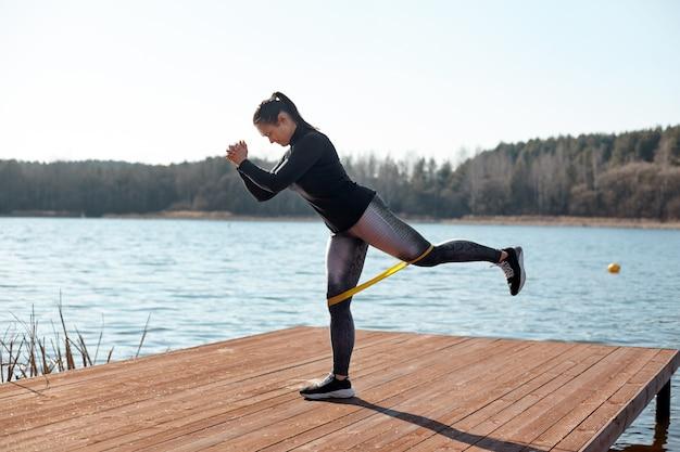 フィットした若い女性は、湖の岸にある桟橋でフィットネスエラスティックバンドを使って運動を行います。健康的なライフスタイルのコンセプト。側面図
