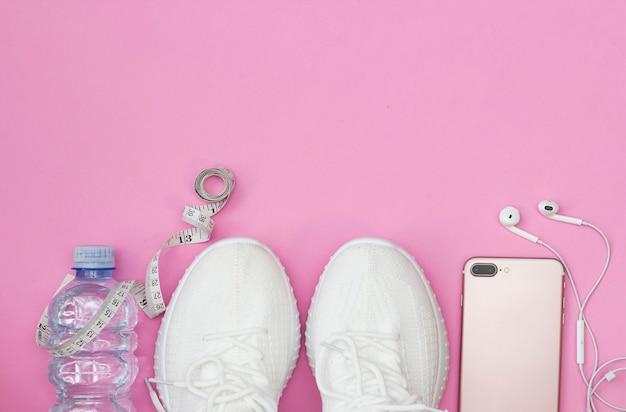 Фитнес-концепция с бутылкой воды, кроссовками, телефоном с наушниками, розовым роликом на розовом фоне. место для копирования.
