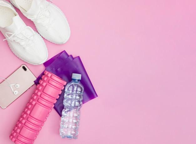 물병, 운동화, 헤드폰이 있는 전화기, 보라색 피트니스 탄성 밴드, 분홍색 배경에 분홍색 롤러가 있는 피트니스 개념. 공간을 복사합니다.