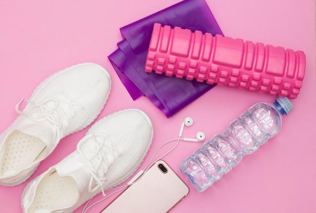 ウォーターボトル、スニーカー、ヘッドフォン付きの電話、紫色のフィットネスゴムバンド、ピンクの背景にピンクのローラーを備えたフィットネスコンセプト。スペースをコピーします。