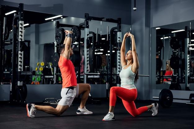 フィットネスカップルは、ジムでの激しいトレーニングの後、筋肉を伸ばします。 Premium写真