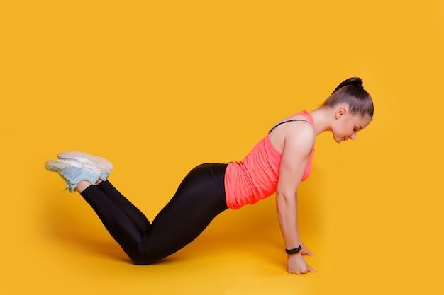 フィットネストレーナーが床から腕立て伏せ運動をする