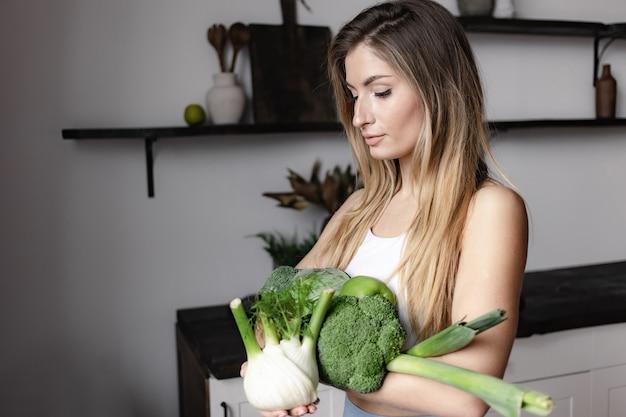 フィットネスの女性は新鮮な生の緑の野菜でいっぱいを保持します
