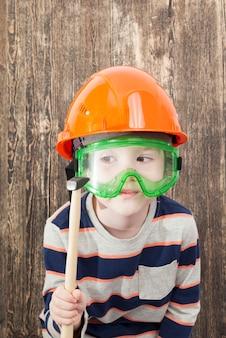 ヘルメットをかぶった5歳の少年が、建設、カーテンの計画を教えている間、ハンマーを手に持っています