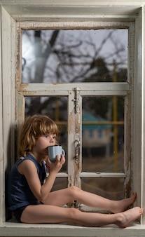 Пятилетний мальчик с грустным видом сидит на ветхом деревянном подоконнике с металлической кружкой в руках.