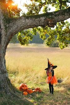 빗자루를 타고 마녀 의상을 입은 5세 소녀가 시선을 돌립니다.