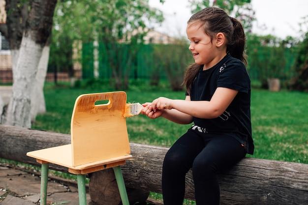 Пятилетняя девочка красит старый стул желтой краской для повторного использования, сидя на бревне в ...