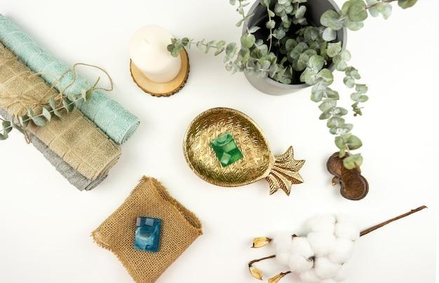 モダンなバスルームの白いテーブルの上に、綿タオル、手作り石鹸、ユーカリの鉢、綿の枝を平らに敷き詰めました。