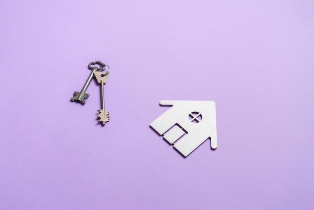 不動産投資のテーブルシンボルのホームキーのフラットレイ