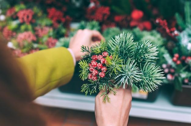 꽃집 소녀는 그녀의 손에 크리스마스와 새해 장식을위한 열매와 전나무 가지를 보유하고