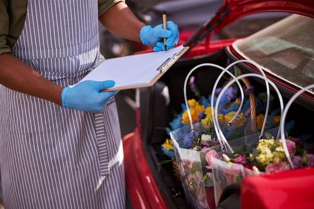 정보를 적을 준비가 된 그의 펜을 들고 파란색 장갑에 꽃집 가게 노동자