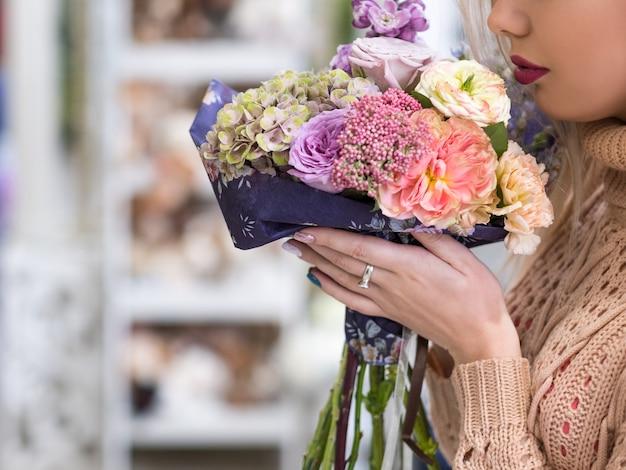 最初のロマンチックな日にフラワーブーケ。繊細なバラのアジサイと牡丹の美しい束を持って匂いを嗅ぐ認識できない女の子