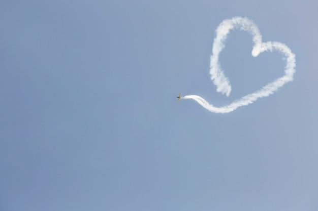 ハートの形の煙で飛んでいる飛行機。バレンタイン・デー。