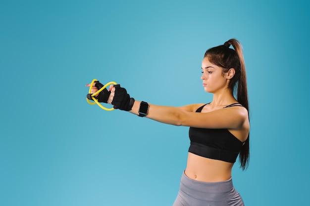 Сосредоточенная спортивная девушка в черном топе протягивает перед собой резинку, чтобы тренировать руки.
