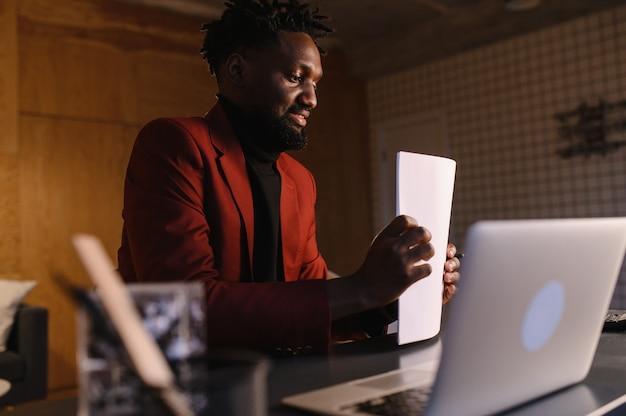 スーツを着た集中した黒人男性がラップトップで作業しています。自宅からのリモートワーク。