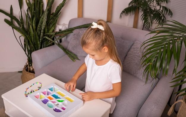 Сосредоточенный ребенок сидит за столом и играет с разноцветными бусами
