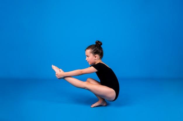 集中力のある小さな体操選手は、テキストの場所と青い背景でバランス運動を実行します