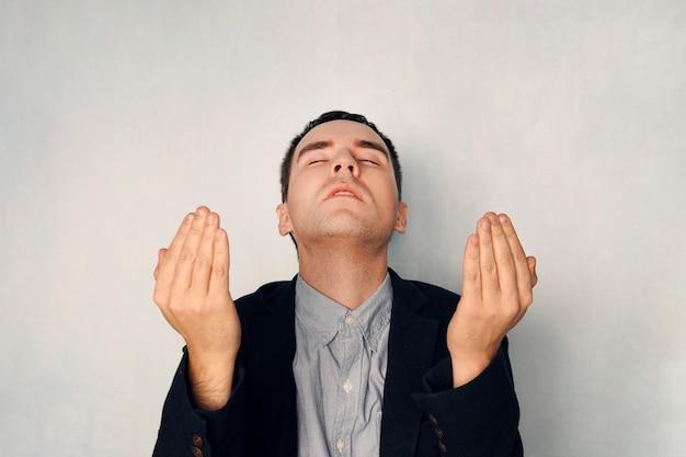 비즈니스 정장을 입은 집중된 남자가 명상을 합니다. 사업가는 기도로 손을 들었다. 하나님의 축복을 간구합니다. 기도와 명상 개념입니다. 파란색 배경