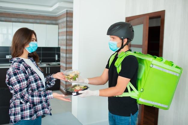 医療用マスクと手袋をした食品配達員が、プラスチックの箱に入った果物と野菜のサラダを若い女性の家に持ってきました。