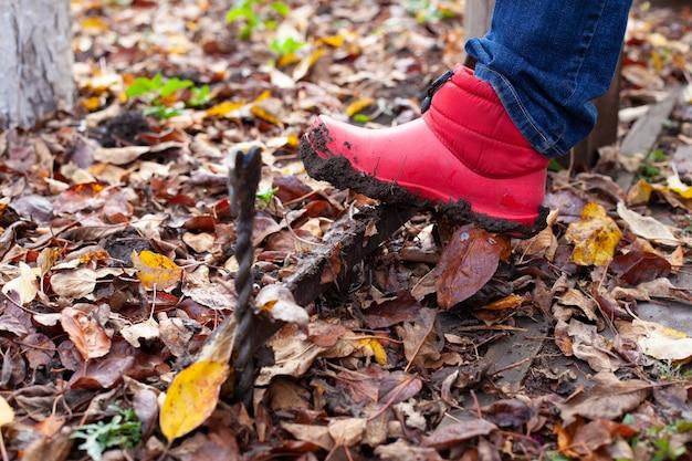 Нога в резиновом сапоге счищает прилипшую грязь с подошвы металлическим кованым скребком для обуви в ба ...