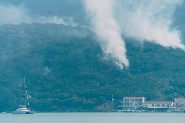 산불이 산에서 내려온 해변의 주거용 건물에 접근하고 있습니다.