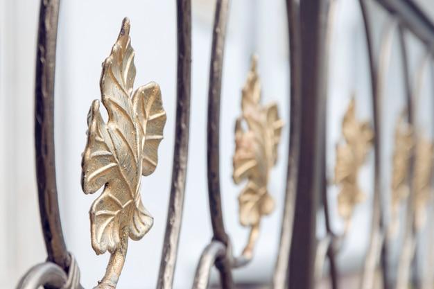 金で覆われた金属製の鍛造フェンス。ブドウの葉。