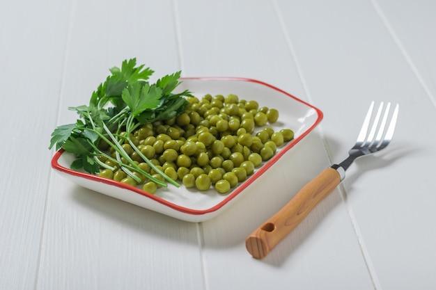 Вилка и тарелка консервированного гороха на белом деревянном столе. диетическое вегетарианское питание.