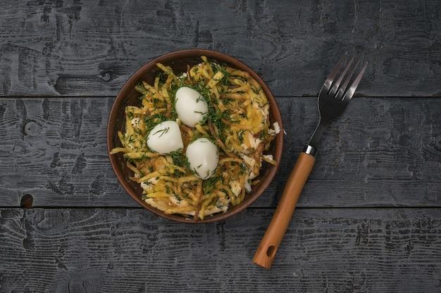 나무 테이블에 메추라기 달걀 샐러드 그릇 옆에 포크