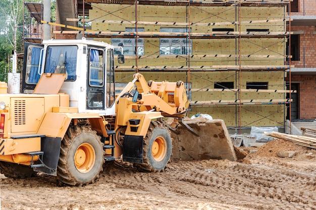 Автопогрузчик на стройке поднимает железобетонную плиту. строительная машина. промышленность.