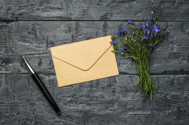 Перьевая ручка, бумажный почтовый конверт и букет цветов на деревянном столе. понятие любовной переписки. плоская планировка.