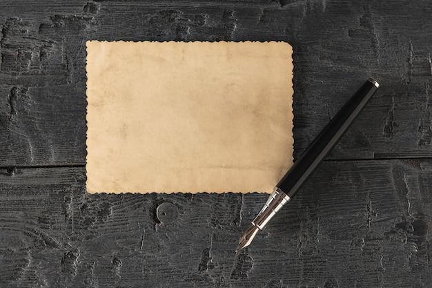 Перьевая ручка и кусок старинной бумаги на черном столе. ретро писчая бумага. плоская планировка вид сверху.