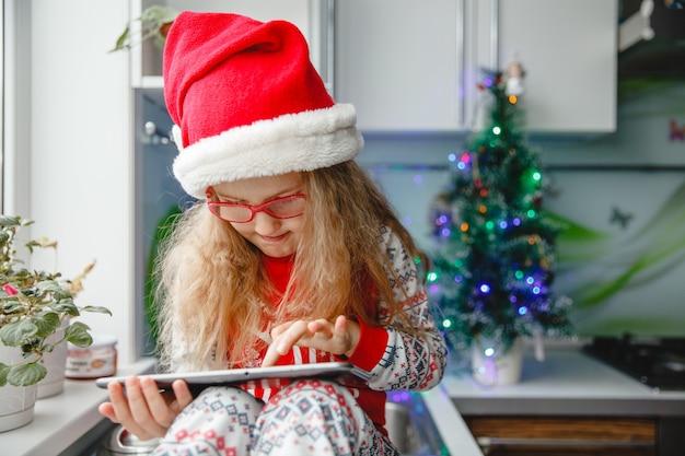 Четырехлетняя девочка в шляпе санты и очках пишет письмо санте на блокноте, сидя на кухонном столе