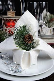 松ぼっくりで飾られたクリスマステーブルセッティングナプキンのかけら