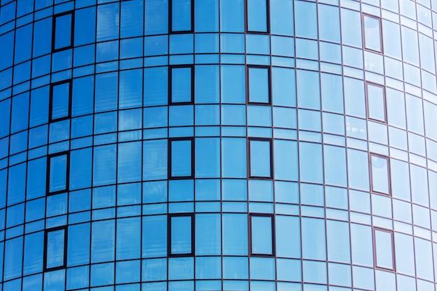 青い空を表示する大きな窓のあるモダンな家の断片。ガラス構造を使用した近代建築_