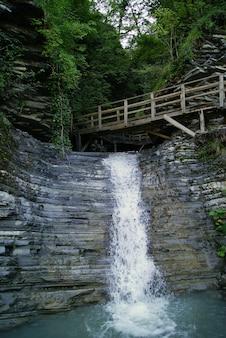 Фрагмент узкого горного каньона с небольшим водопадом и деревянными трапами с перилами.