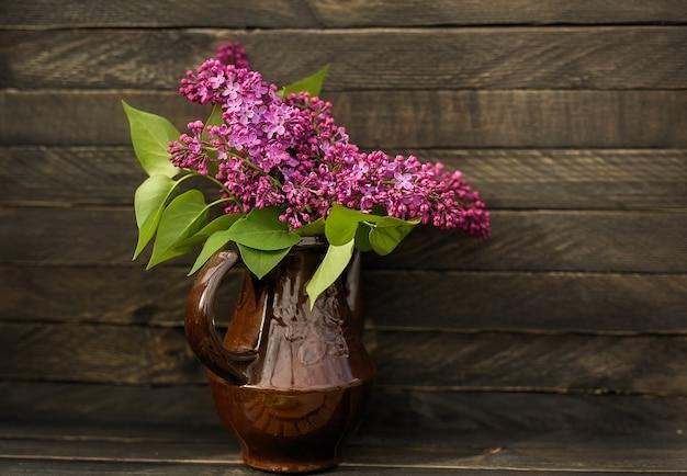 라일락의 향기로운 꽃다발은 소박한 스타일의 나무 배경에 작은 분홍색 용기에 선다.