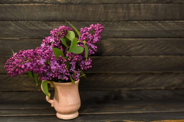 라일락의 향기로운 꽃다발 나무 배경에 작은 분홍색 용기에 서
