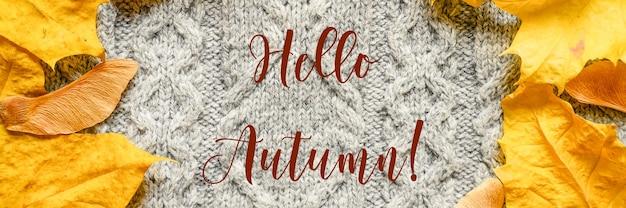 Каркас из осенних опавших оранжевых кленовых листьев и семян и красного каштана на фоне уютного осеннего серого вязаного шерстяного свитера. текст «привет осень» шрифтом офл. знамя
