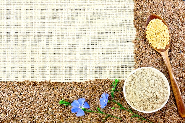 茶色と白の亜麻仁のフレーム、ボウルに亜麻の粉、粗い織物の背景に青いリネンの花
