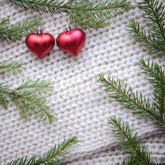 Рамка из зеленых веток елки и двух красных сердечек на белом вязаном фоне