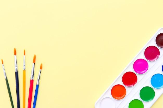 Рамка канцелярских товаров на желтом фоне, вид сверху плоского макета кистей и акварелей. концепция раннего развития, творчества и изобразительного искусства.