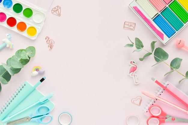 ピンクの背景にパステルカラーの学用品のフレーム、テキストの場所。学校に戻ります。事務用品。フラットレイ、上面図、コピースペース。