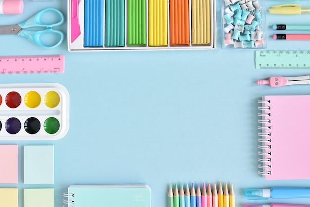Рамка школьных принадлежностей в пастельных тонах на голубой поверхности, место для текста
