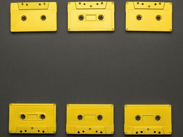 검정색 배경에 노란색 테이프 카세트의 프레임. 플랫 레이.