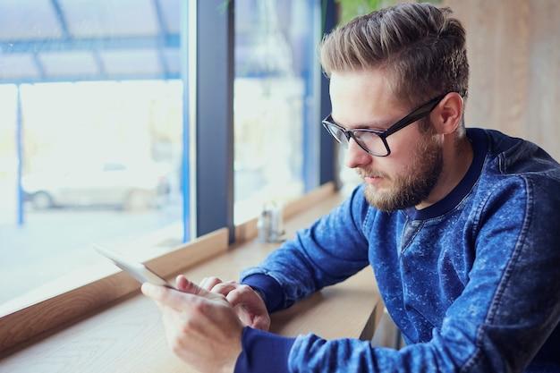 그의 손에 태블릿 프리랜서 hipster 남자는 창이 카페를 작동합니다.